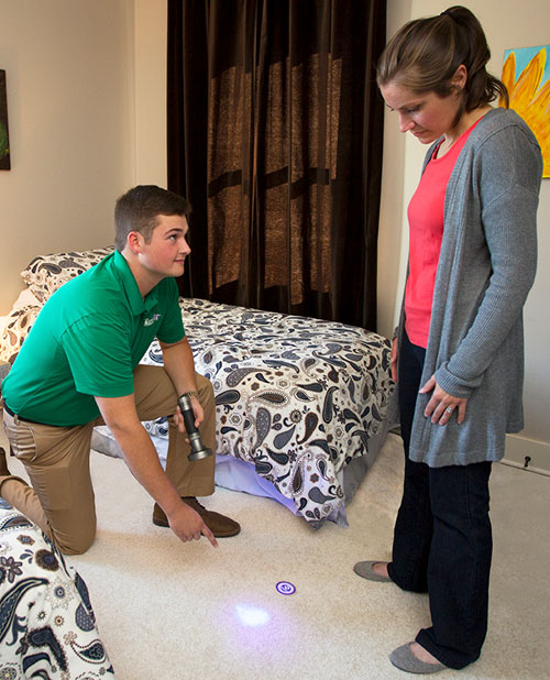 chem-dry technician showing woman pet urine stain on carpet